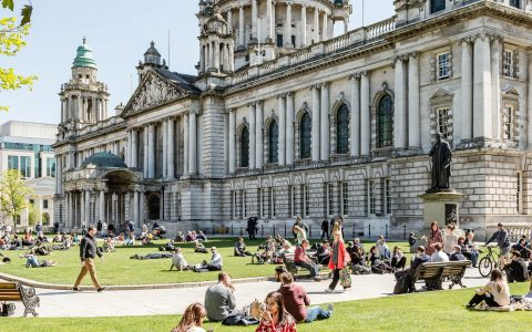 People in the sun outside Belfast City hall
