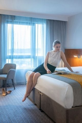 Woman sitting on bed in king room at Maldron Hotel Sandy Road
