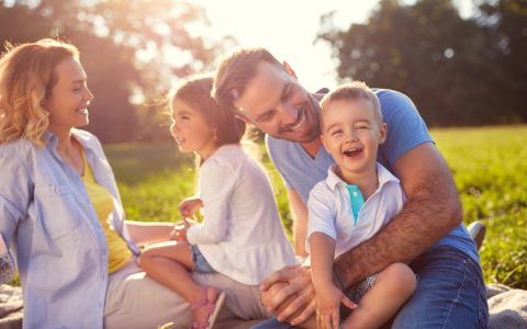 Family with 2 young kids in the park in summer
